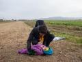 Begunci na poti iz Rigonc do 12km oddaljenega zbirnega centra v Brežicah. Moški pobira otroka.