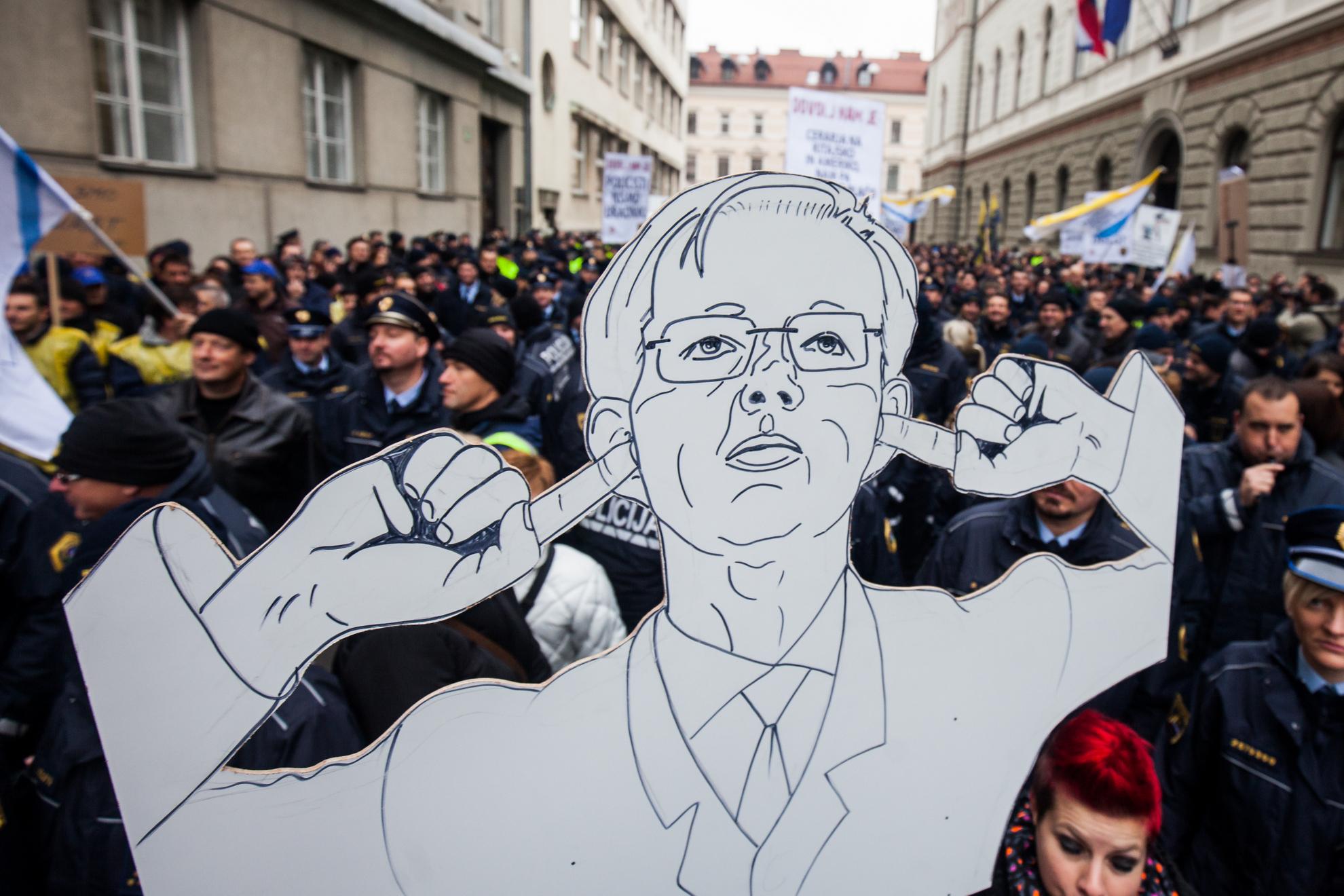 Ljubljana, Stavka policistov. Transparent premieja Mira Cerarja pred stavkajočimi policisti na Gregorčičevi ulici pred vlado.