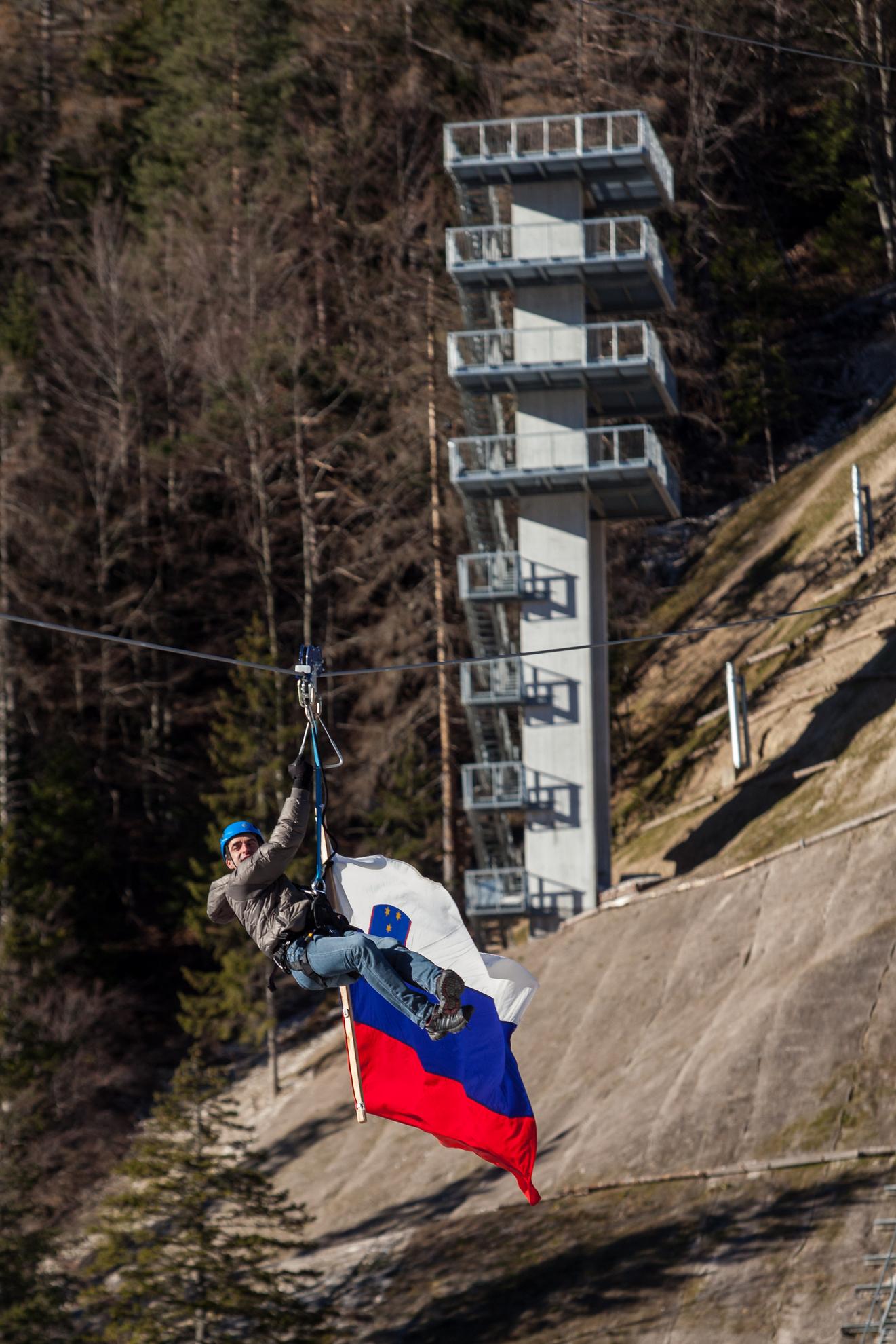 Planica. Otvoritev Nordijskega centra Planica in obisk vlade na gorenjskem. Franci Petek se spušča  po zip-line s slovensko zastavo nad letalnico v Planici.